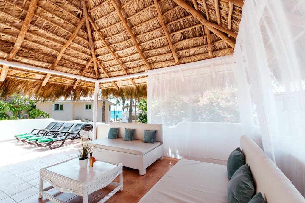 Rooftop terrace: sitting area, dining area, BBQ, sun chairs, partial ocean view