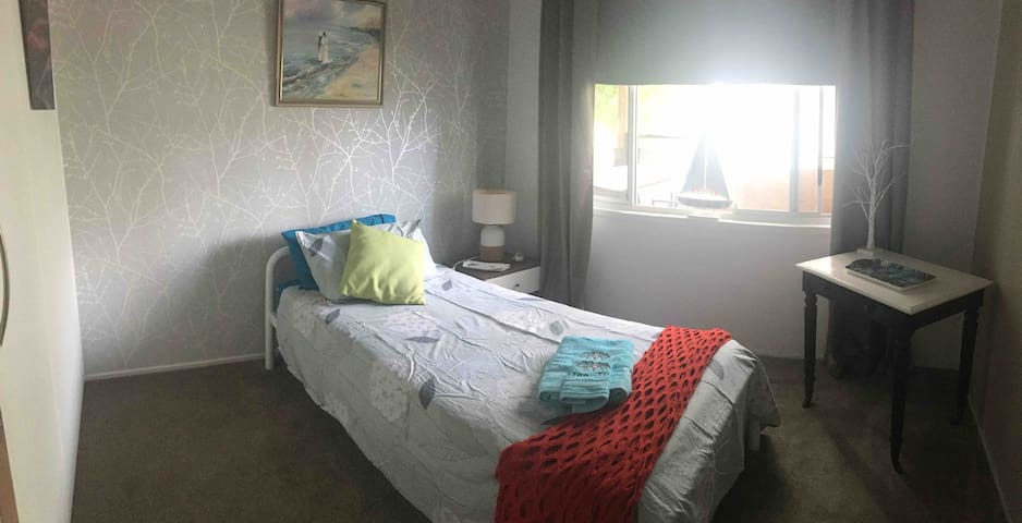 This is our single Portside room.  It overlooks our deck  This lovely room has a wardrobe and built in chest of drawers for your convenience.  It has a fanlight that is operated by a remote control which is situated on the bedside table with a lamp
