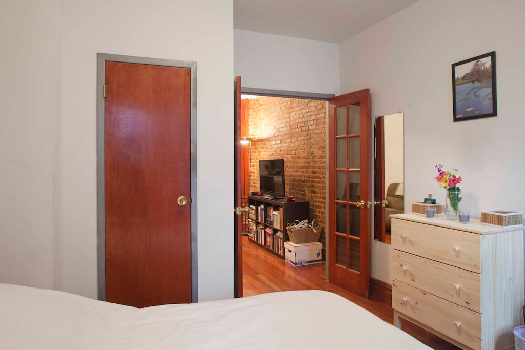 Bedroom has french doors, closet, and dresser.