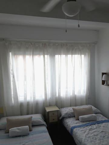 Habitación con mesita de noche, lámpara, ventilador de techo, dos camas de 0,90 × 2 mts.  y armario.