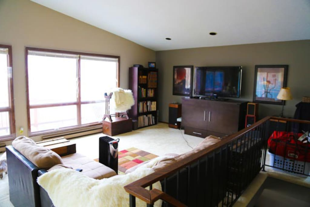 The spaceous living room features vaulted ceilings, a murphy bed and comfy couch invite snuggling as you watch the Sunset, lake fun or the TV.