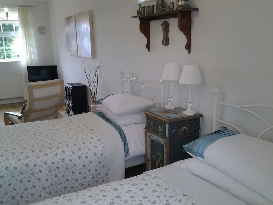 bright spacious twin bedded room with tv and sitting area