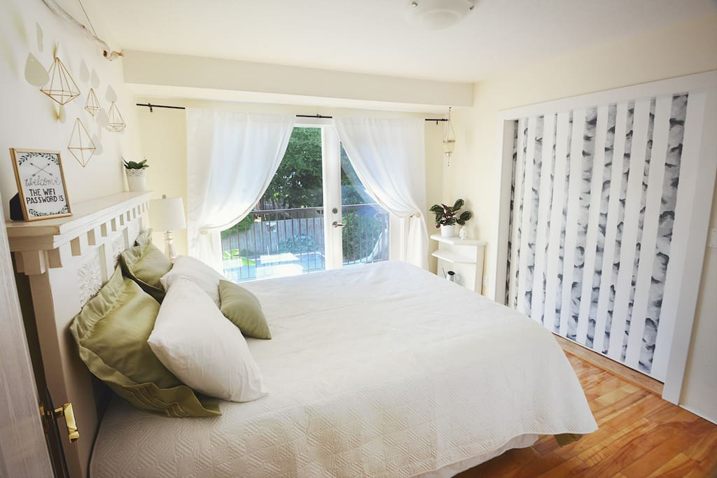 Our beautifully designed Birch Room with queen bed and balcony access. The birch mural is the sliding door that can be opened to be connected to the Fireplace Room.