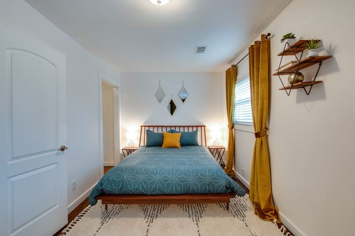 Luxurious master bedroom with a cozy queen bed and plush pillows.