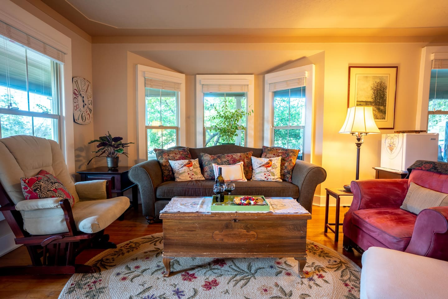 Living room with vintage furnishings and bay window.