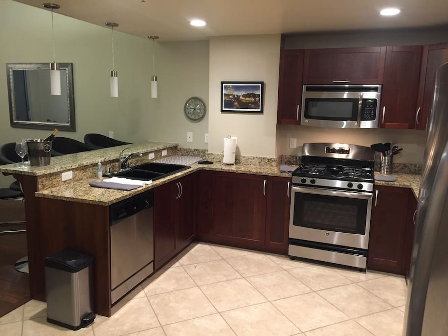 Double sink with garbage disposal, stainless steel appliances and granite countertops.
