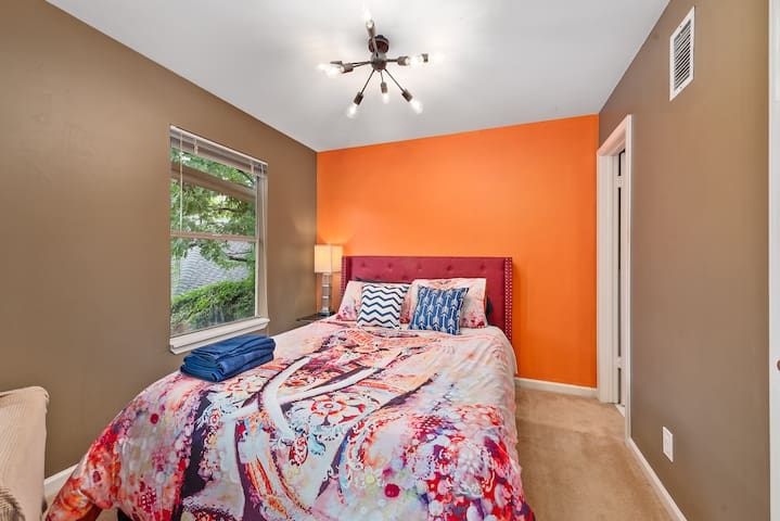 A queen bed downstairs with modern lights and popped accent orange room