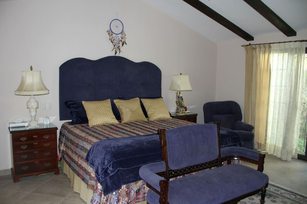 King bed with private walled patio to right, and vaulted ceilings.