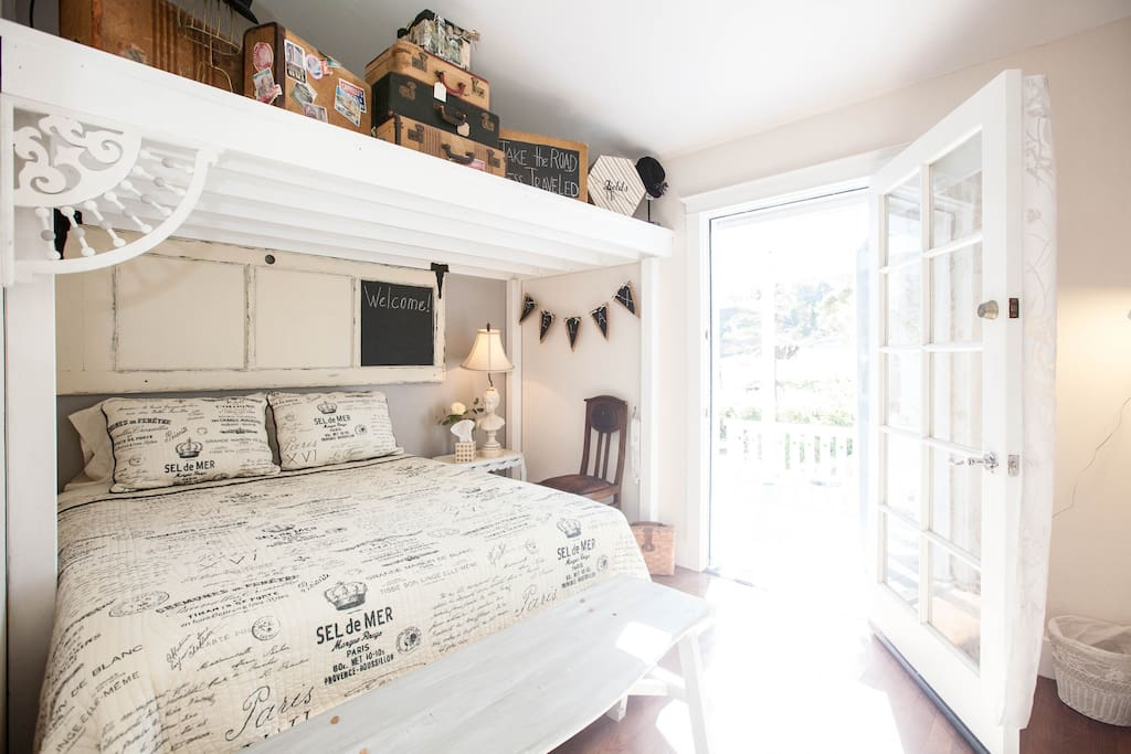 Light and airy bedroom has a queen bed. The loft has a vintage suitcase collection for decoration.