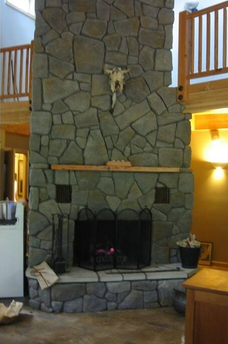 Massive fireplace sits between the kitchen, dining room, and living room areas.