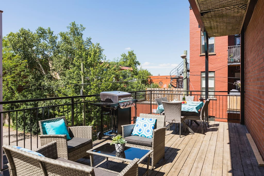 Sunny terrace with table, BBQ and outdoor furniture