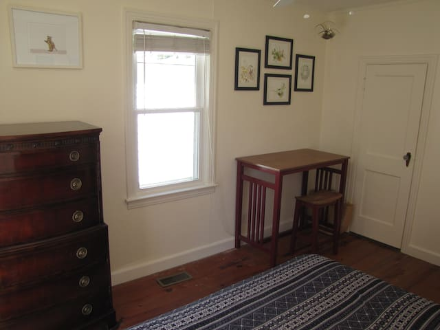 It's a small room, but has a desk area, a chest of drawers, and its own tiny half-bath.