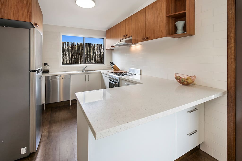 new kitchen with modern appliances and stone bench top