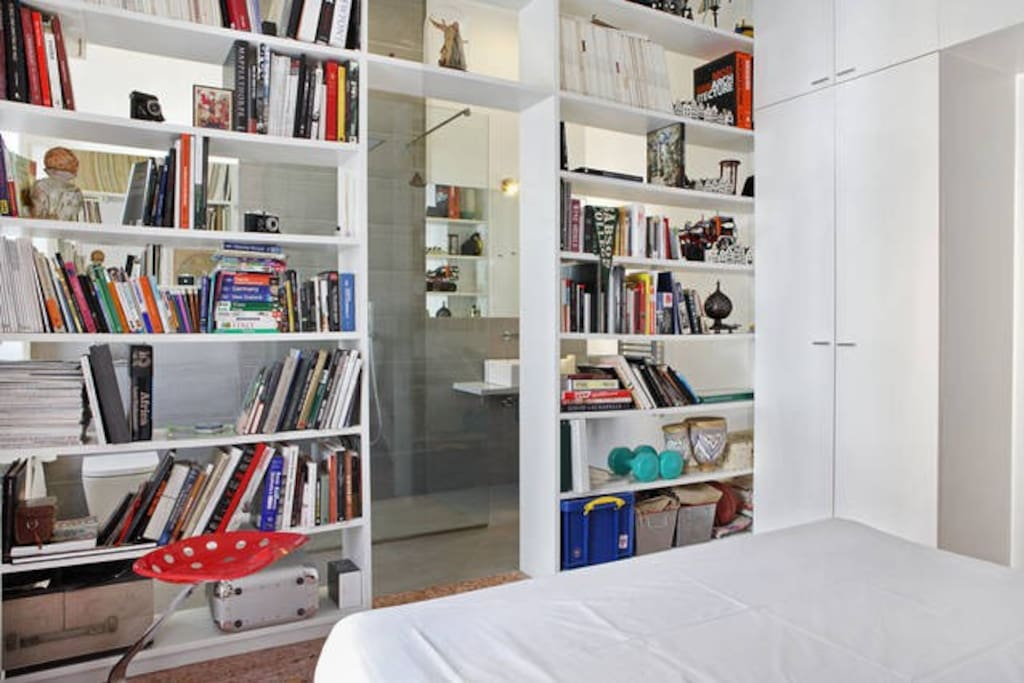 A large book shelf archway separates the bedroom area from the ensuite bathroom