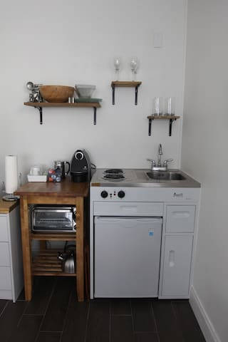 Mini-fridge, 2-burner stove-top, toaster oven, Nespresso coffee machine.