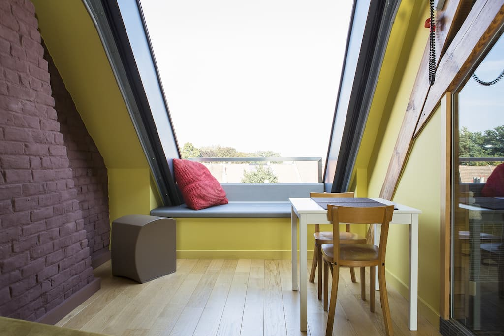 Roof window opens completely and creates a small sitting bench in open air.