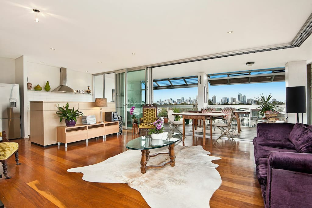 Living area opening onto terrace, Harbour Bridge and Sydney CBD