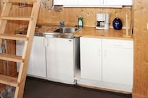 Kitchen area with refrigerator, sink, 2 cooking plates. There is also a microwave (not present when picture was taken).