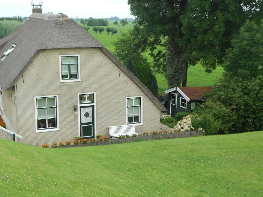 Voorzijde met aan de rechter zijde het tuinhuis met fietsen en tuinstoelen.