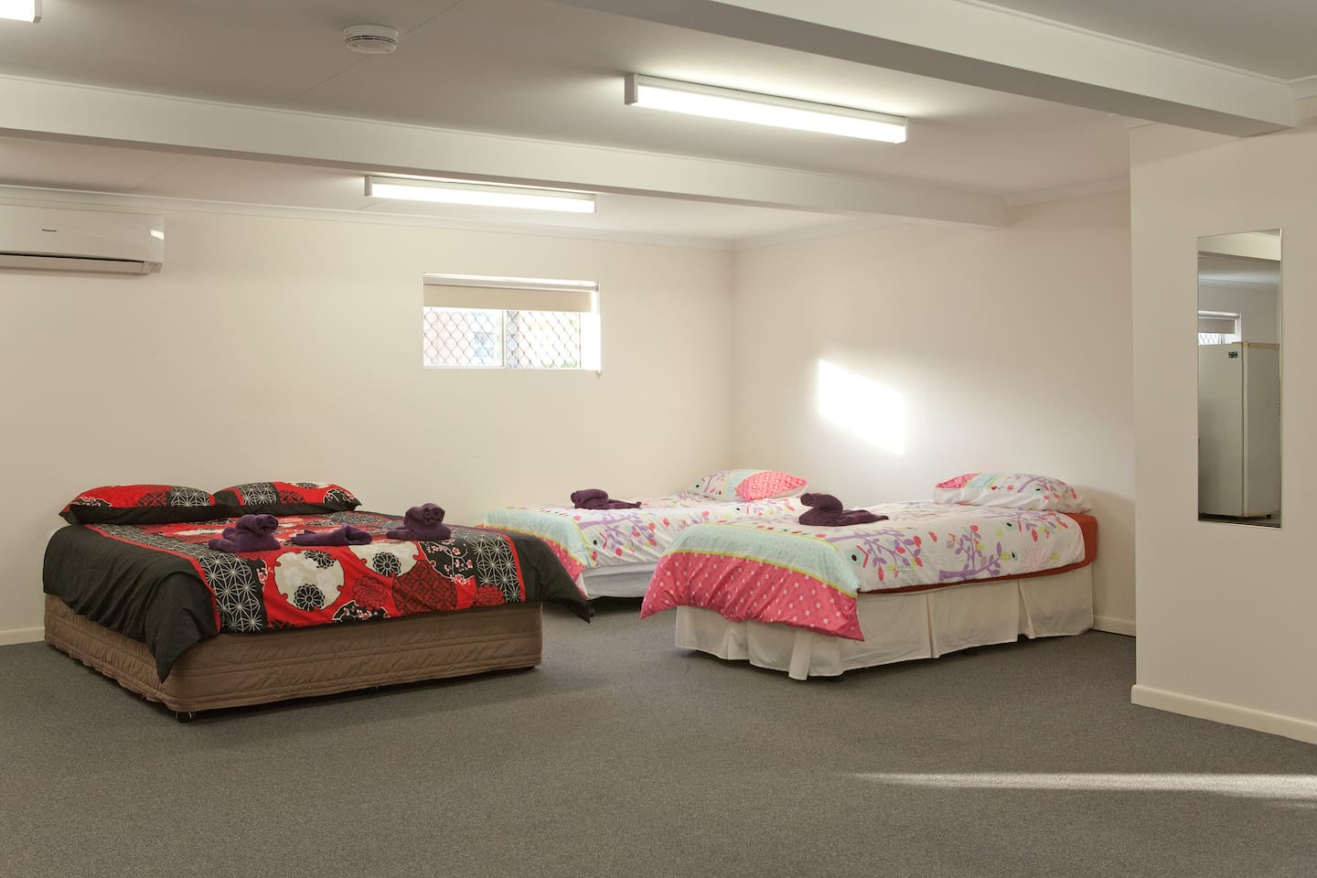 1 Queen size bed and 2 single beds with towels and linen.
