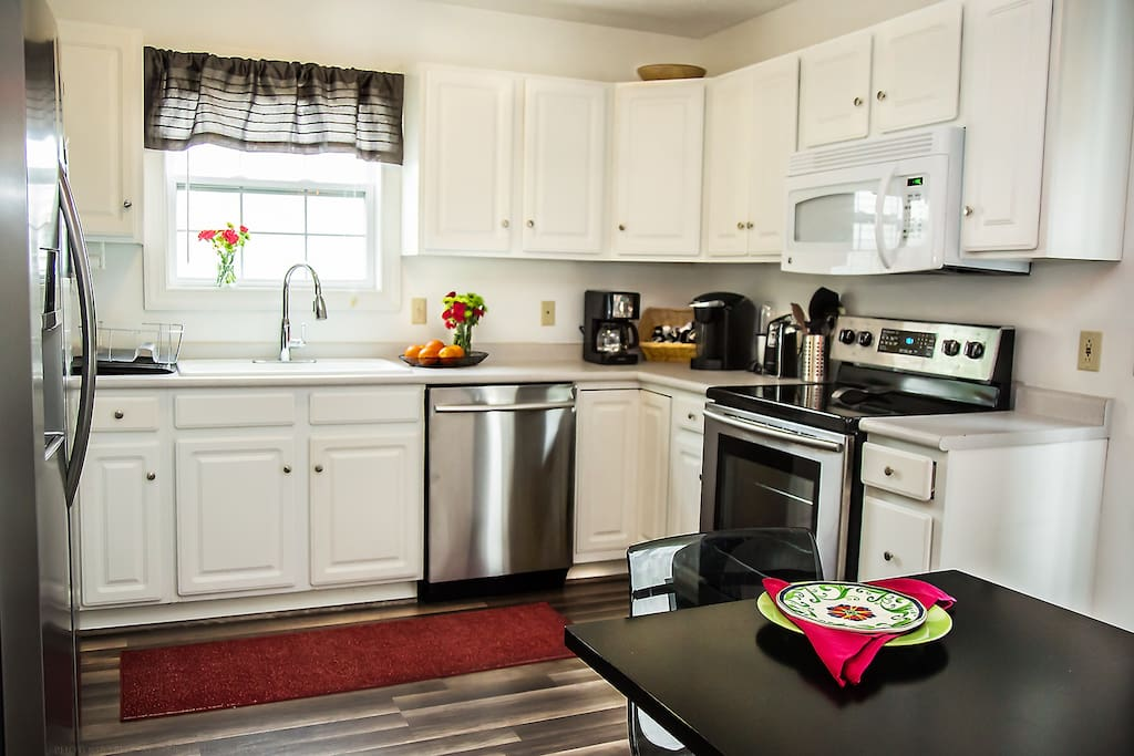 Kitchen with dishwasher, electric stove, microwave.