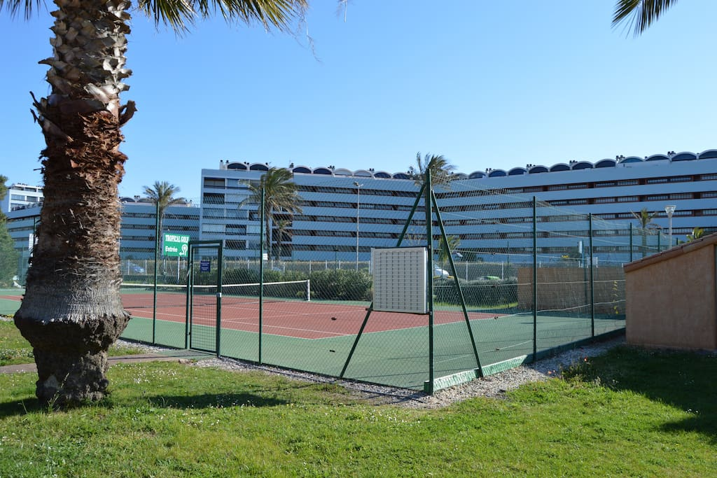 Un terrain de tennis bien entretenu avec tableau de réservation.