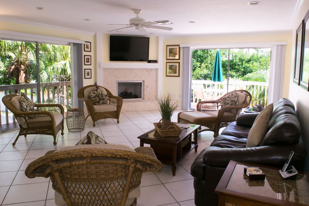 """Bright, Spacious Living Room w/ 55"""" Flat Screen and Coral Stone gas Fireplace surrounded by wrap around Deck."""