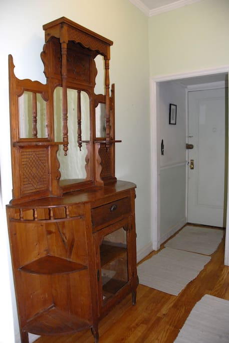 Entry foyer with roomy coat closet.  This piece of antique furniture has been moved into the living room, and this space is now used as dinette.