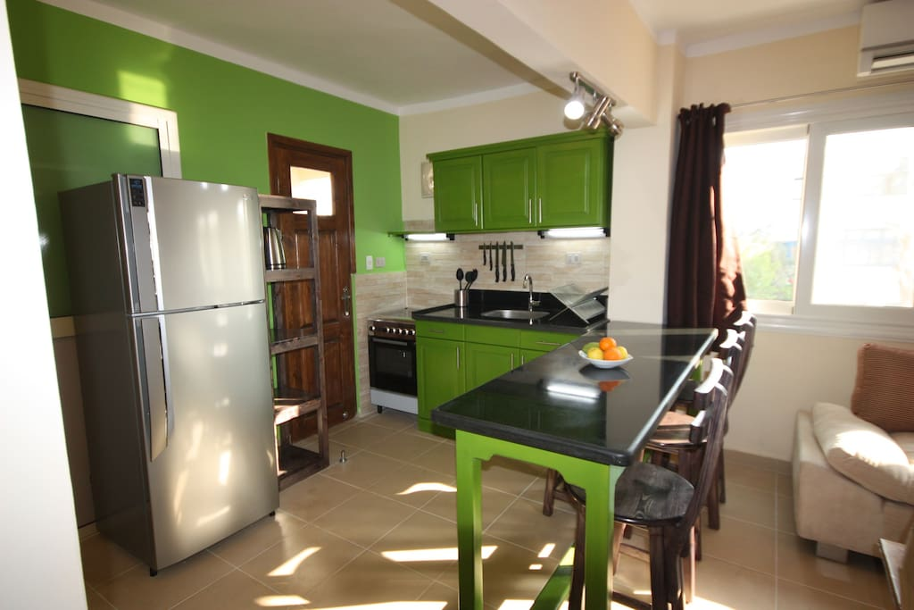 Modern kitchen with gas oven and 4 hobs, large fridge/freezer, kettle, toaster, juicer and coffee machine.