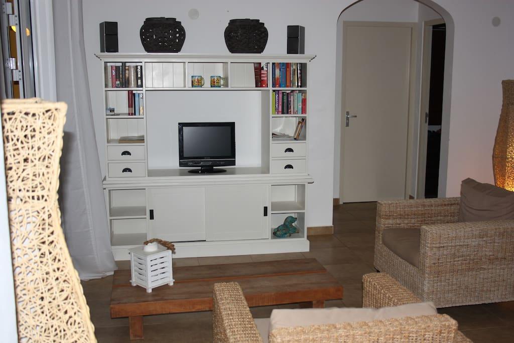Riante, in tropische stijl ingerichte woonkamer met flatscreen TV, DVD speler en Radio/CD speler.