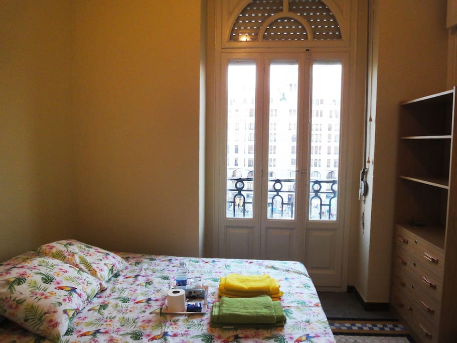 Habitación con cama de matrimonio, balcón y vistas al centro de Valencia