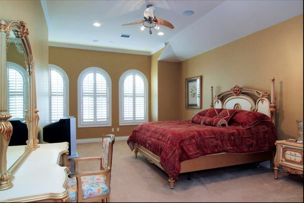 another guest suite with arched windows, ceiling fan, carpet and private bath.