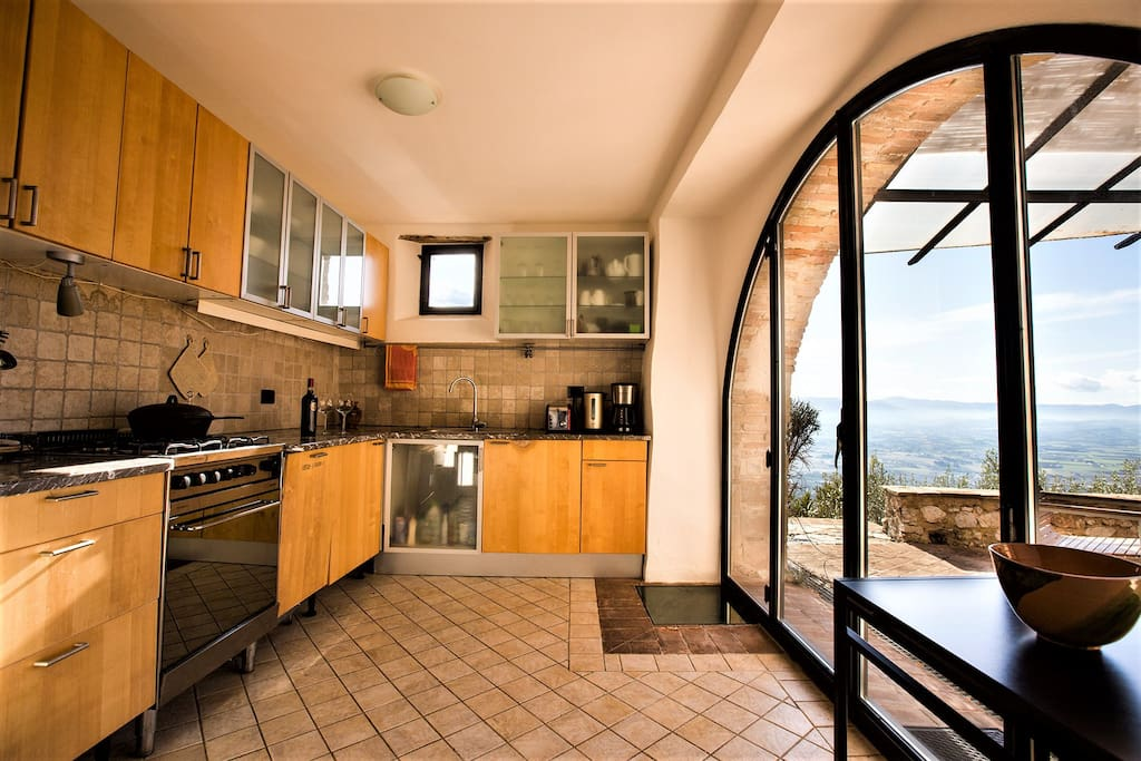 Kitchen Through the large arched doors of the kitchen, one looks out to the private terrace and the tranquility of the olives groves. The kitchen is fully equipped with a dishwasher, stove, oven, a large refrigerator, microwave and everything you will need to create delicious meals at home while enjoying the sunset.