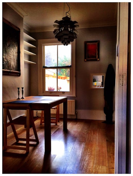 A dining room with dining table for up to 8 guests surrounded by eclectic artwork.