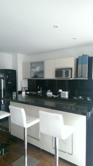 Moderna y amplia cocina con una barra-comedor incorporada.