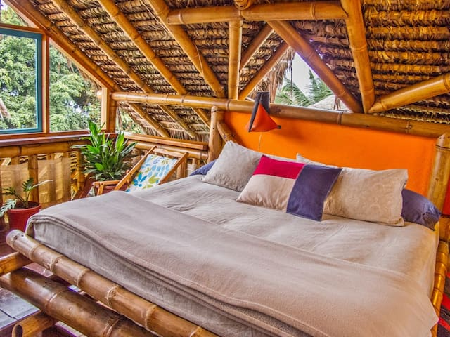 California king in master bedroom (photo taken without mosquito net to show bamboo architecture and windows, but all beds have nets!).