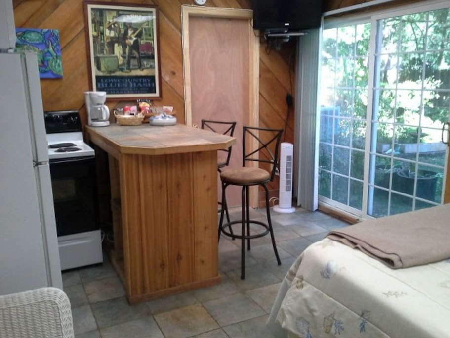 Island bar with  fridge ,stove,flat screen TV and nice view of the garden.