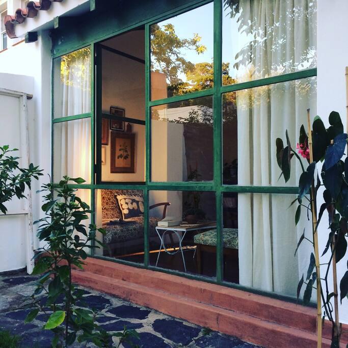 La galería de Siesta una tarde de sol. Este espacio cuenta con un pequeño sillón, una mesita de café y una banqueta, y tiene muy buena luz natural para leer.
