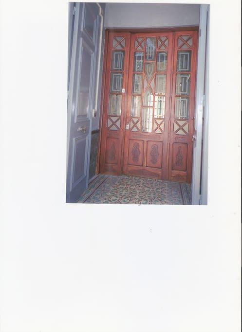 Acceso al Edificio -  con puerta cancel aratesanal, tallada  de madera de roble con vidrios repartidos, que da acceso al zagúan