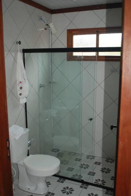 Banheiro espaçoso com box blindex