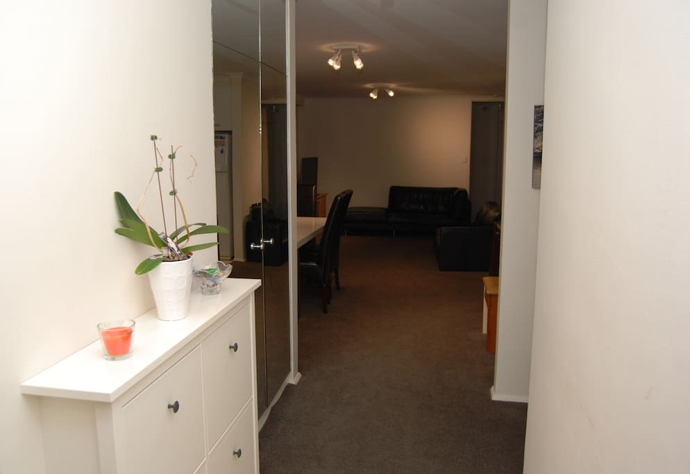 Tiled entrance with shoe storage leads into open plan lounge/kitchen/dining area