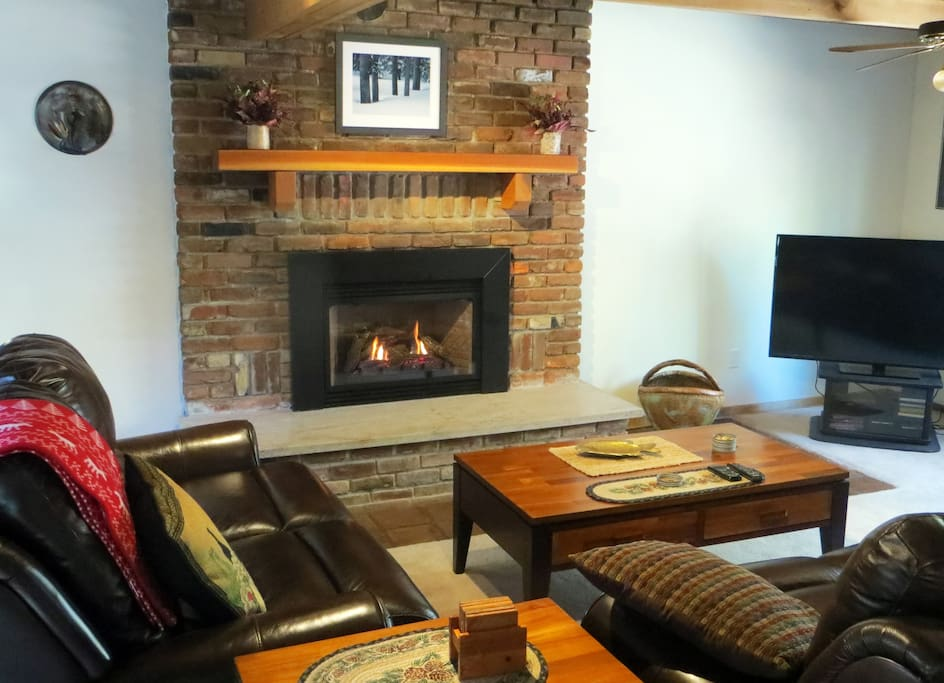 Living room with leather couches, big screen TV, gas fireplace