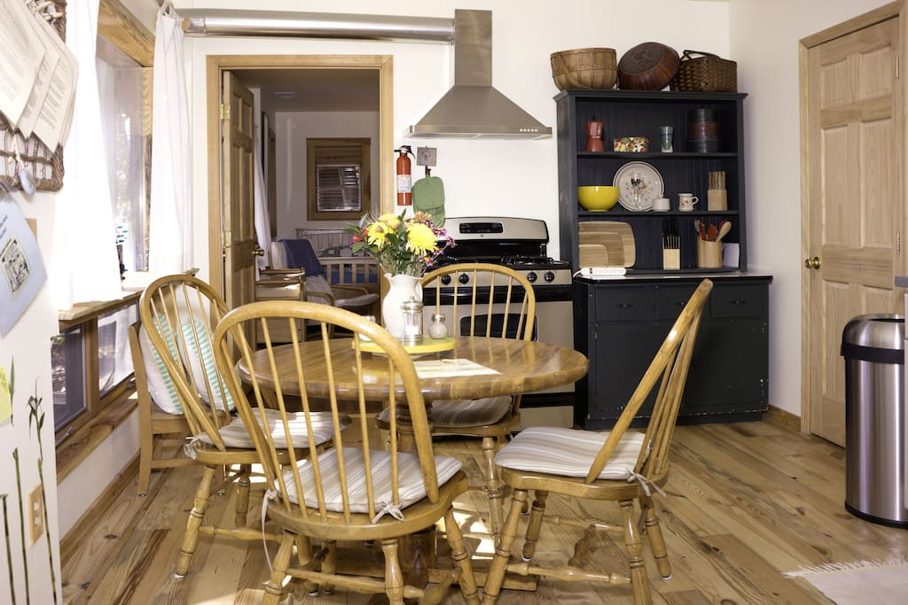 Dining area facing yellow bedroom, antique cupboard and large window facing river on left.