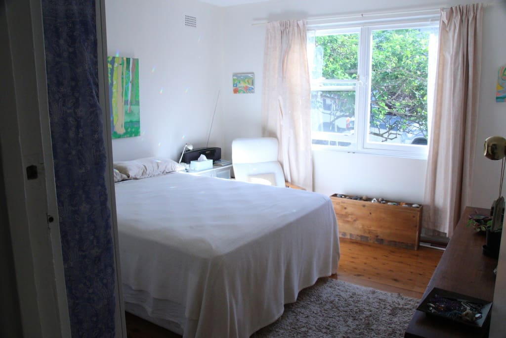Main bedroom with queen-size bed and morning sun.