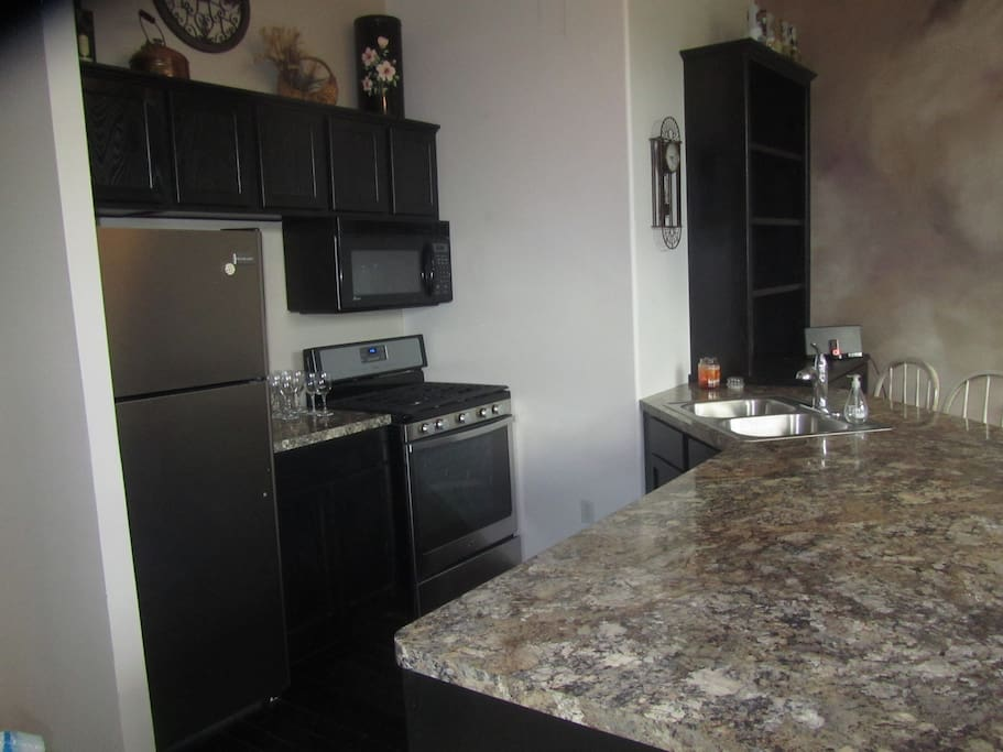 Full kitchen with stove, microwave, refrigerator, coffee machine, dishes & cooking tools