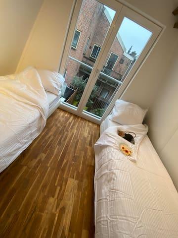 Slaapkamer 2 met 2x een persoons bed met uitzicht op het dakterras
