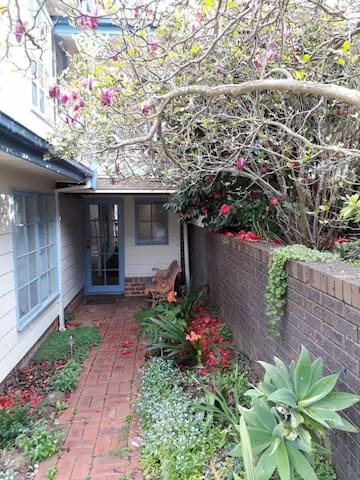 Front entrance to cottage, stroll in under the gorgeous Magnolia Tree.