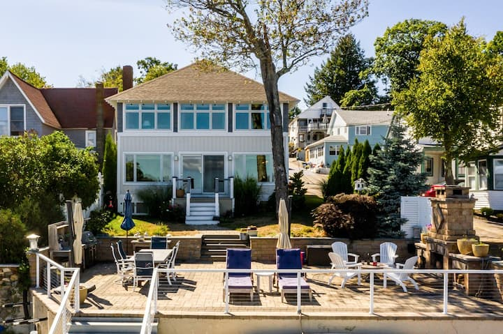 Waterfront home in Weirs Beach with 26' boat dock, outdoor fireplace, and private sandy beach