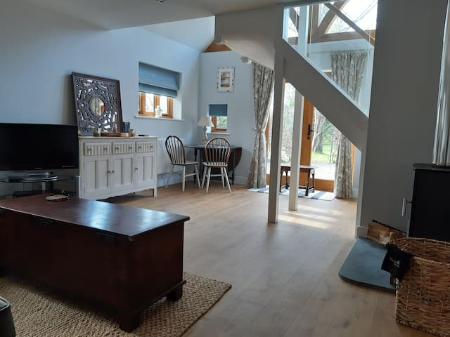 Open plan sitting and dining room with glazed stairs leading to the mezzanine floor.