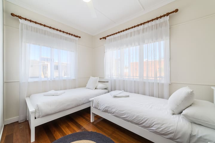 The third bedroom includes two single beds, both with premium linens, air-conditioning and wardrobe space.